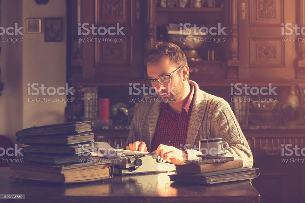 Young man writing on old typewriter. stock photo