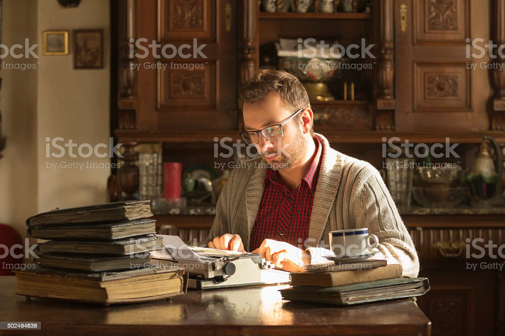 Young man writing on old typewriter. stock photo