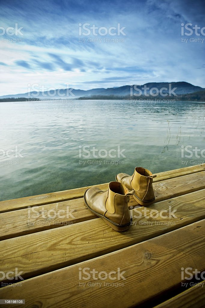 Young Man's Boots Sitting on Edge of Lake Dock royalty-free stock photo