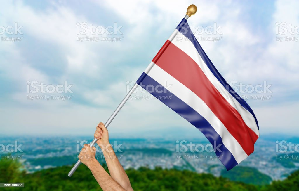 Young man's hands proudly waving the Costa Rica national flag stock photo