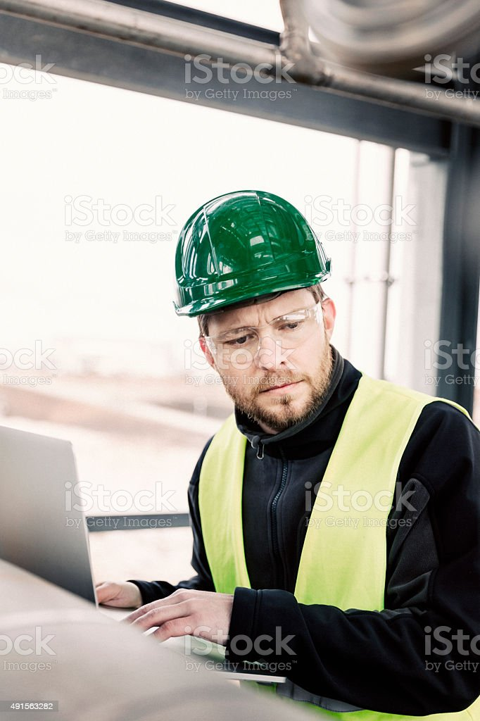 Young manual worker looking away while working on laptop stock photo