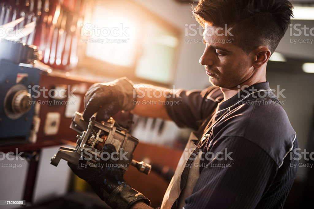 Young manual worker repairing electric motor in a workshop. stock photo
