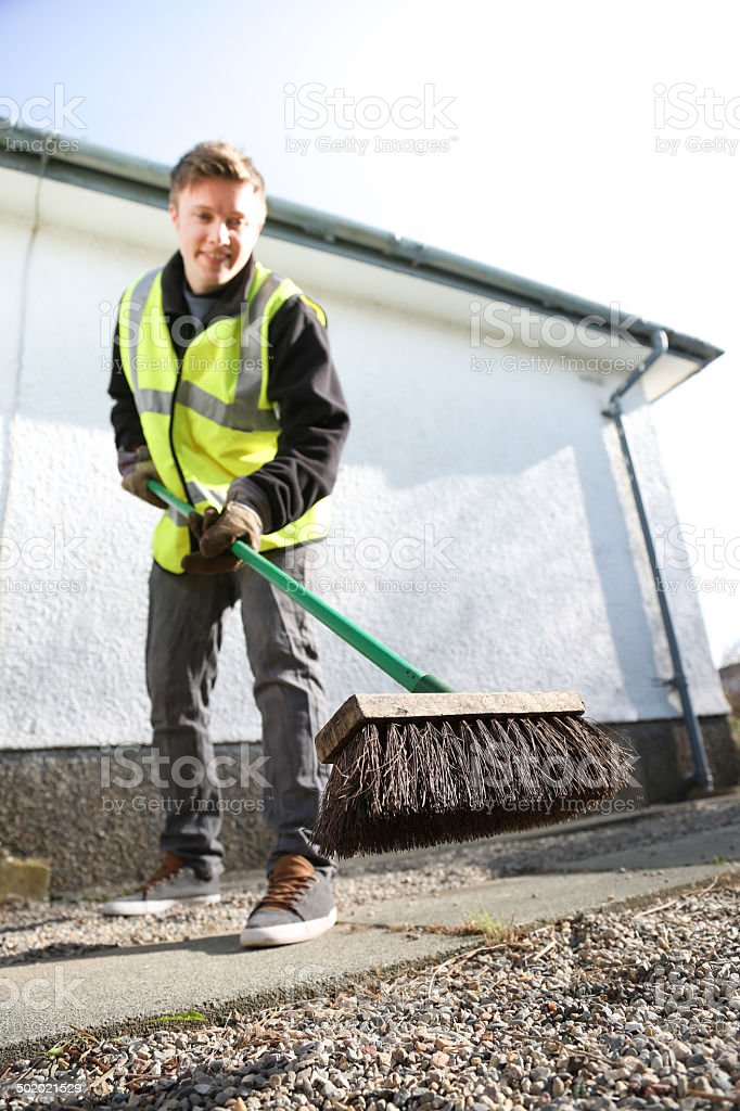 Young manual worker sweeps a path stock photo