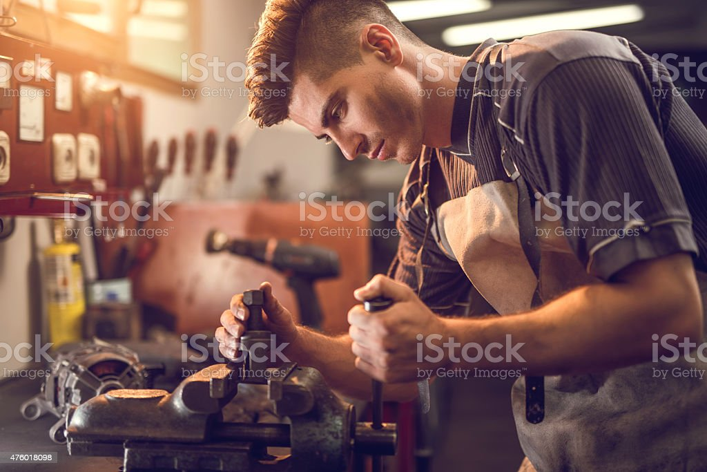 Young manual worker working on a clamp at workshop. stock photo