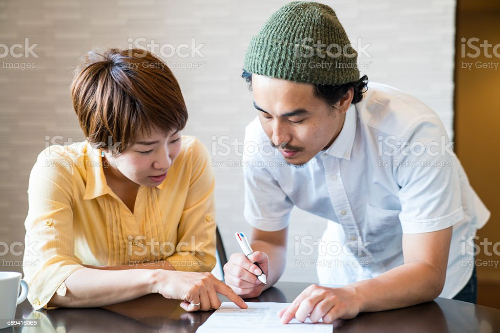 Young married couple filling out important paper documents stock photo