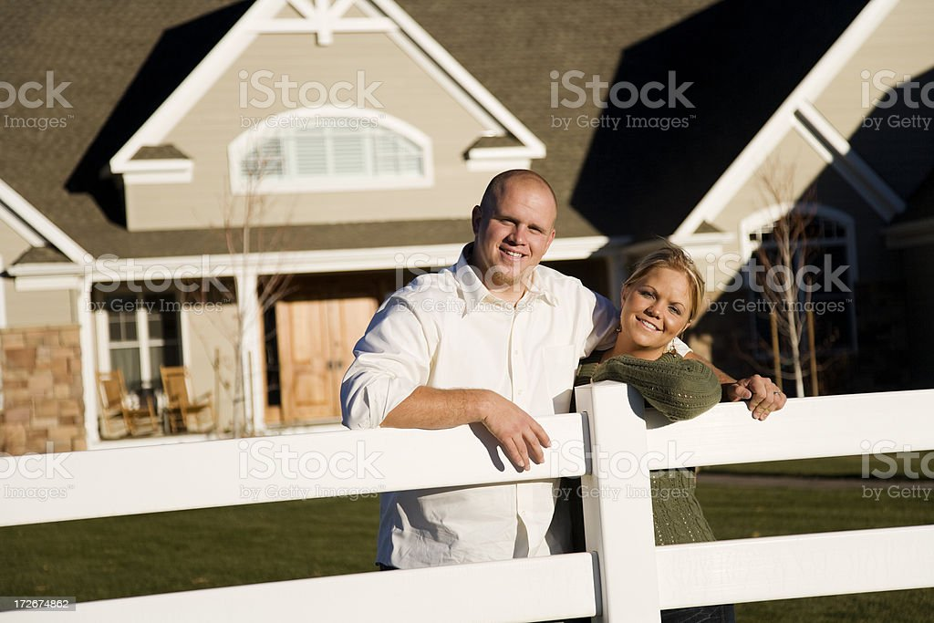 Young Married Couple Leaning on Fence at Home royalty-free stock photo