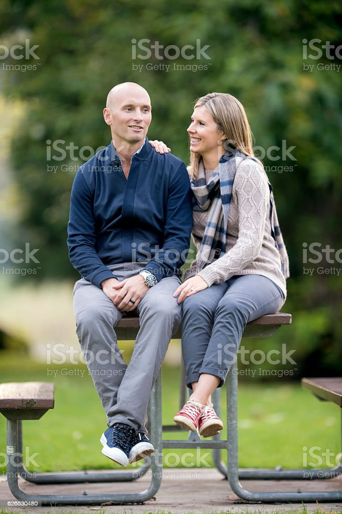 Young married couple sitting together on a picnic table stock photo
