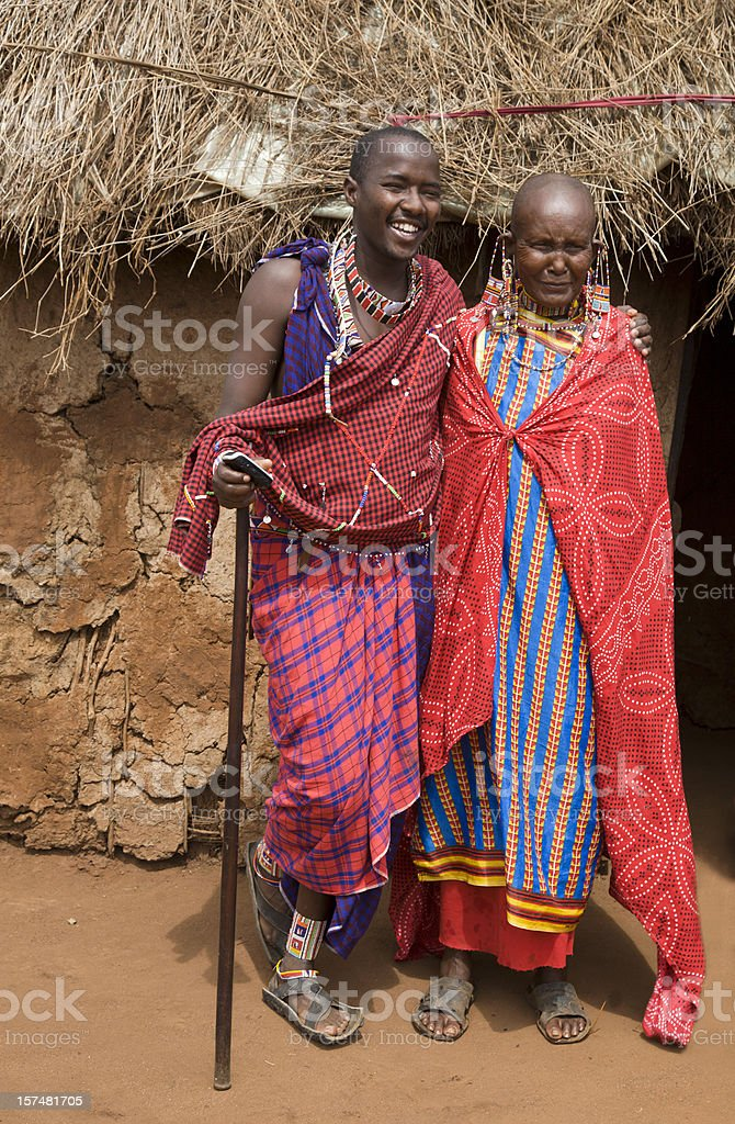 Young masai with old female relative outside her mud hut. stock photo