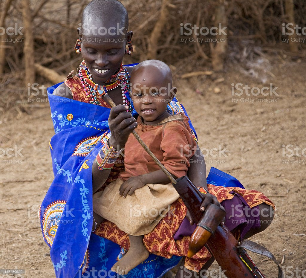 Young Masai woman with child cleaning calabash. Kenya. stock photo