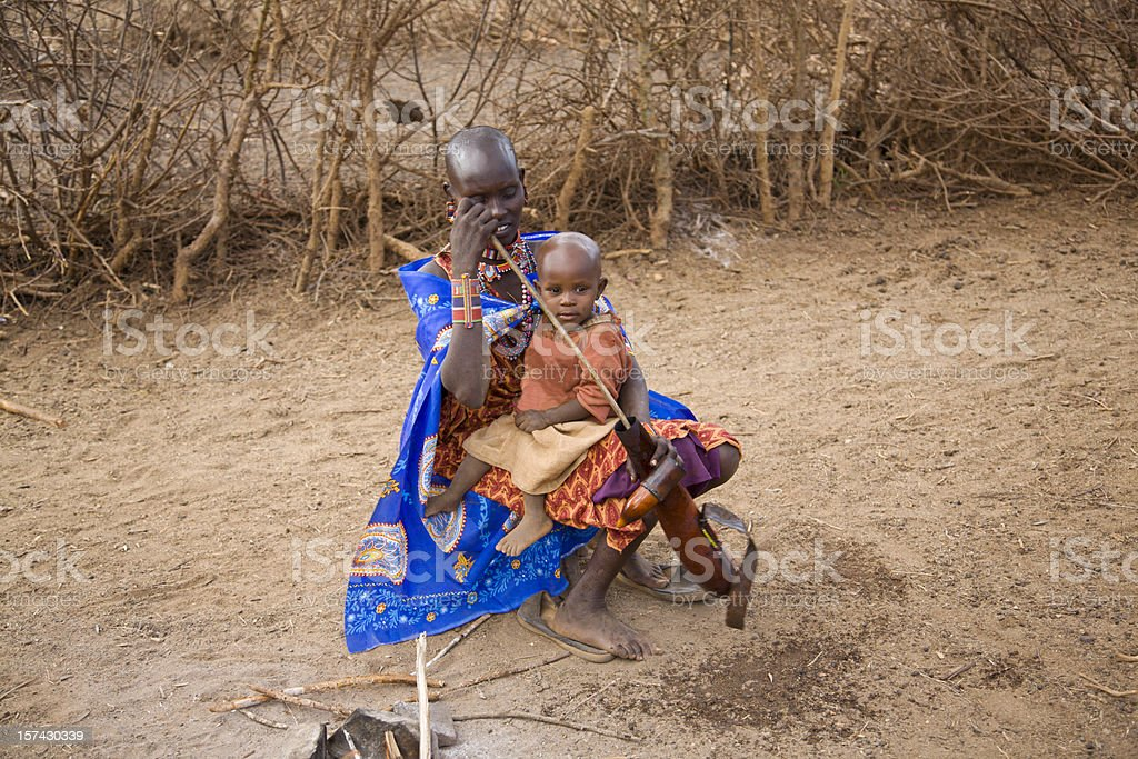 Young masai woman with child cleaning calabash. stock photo