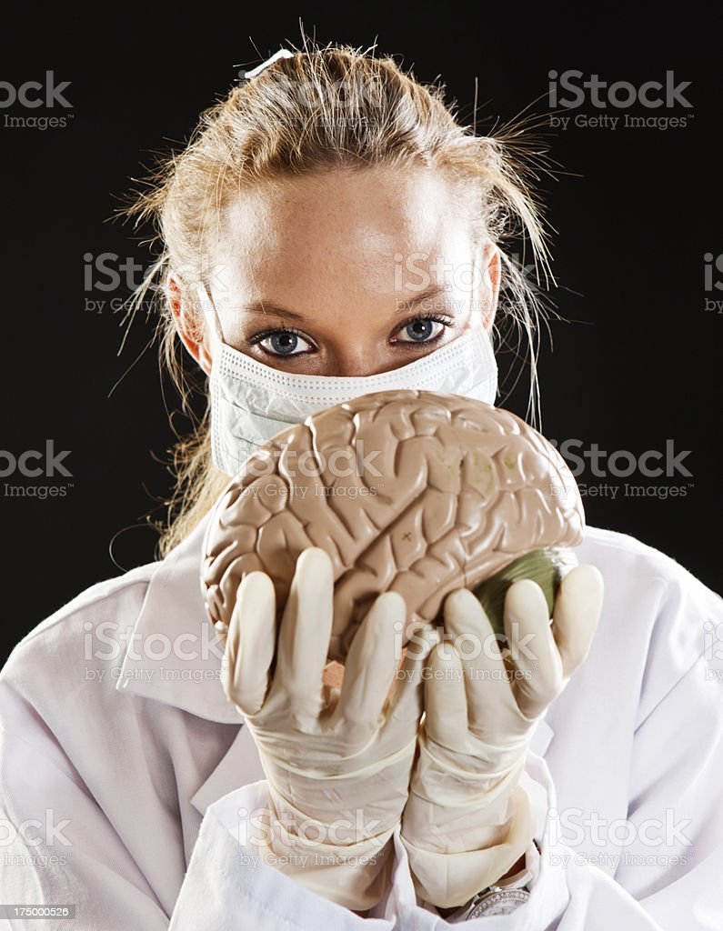 Young. masked female doctor holds up model brain stock photo