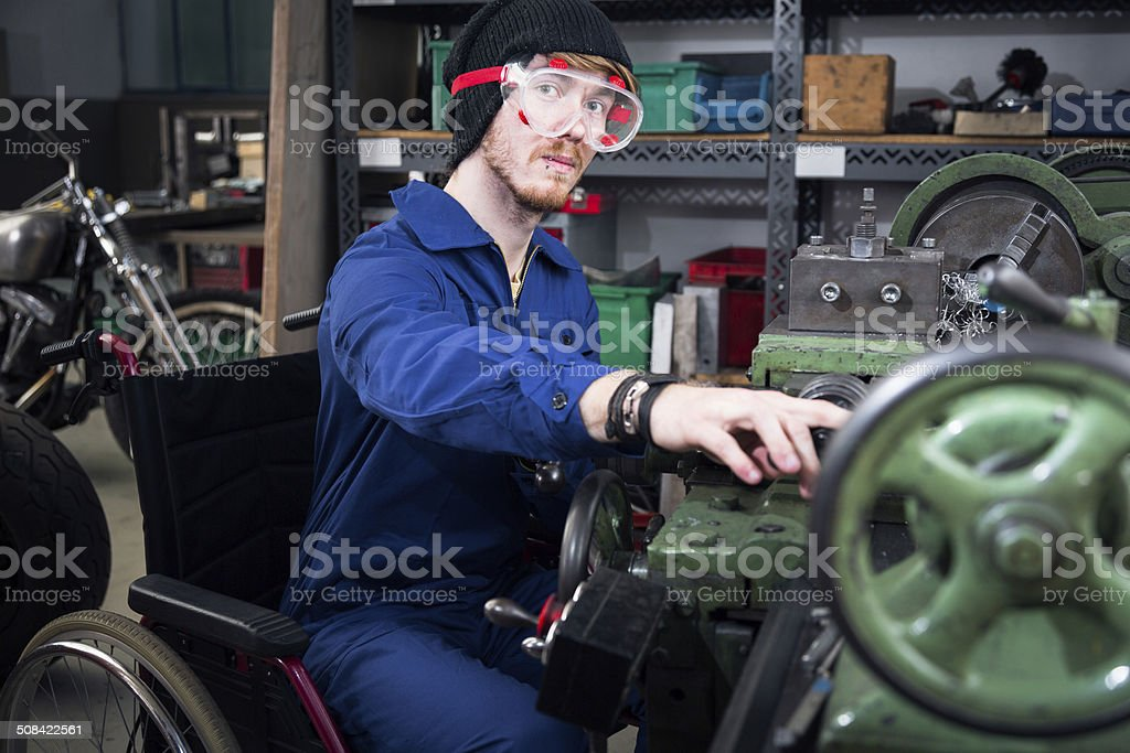 young mechanic / apprentice in wheelchair working on turning lathe stock photo