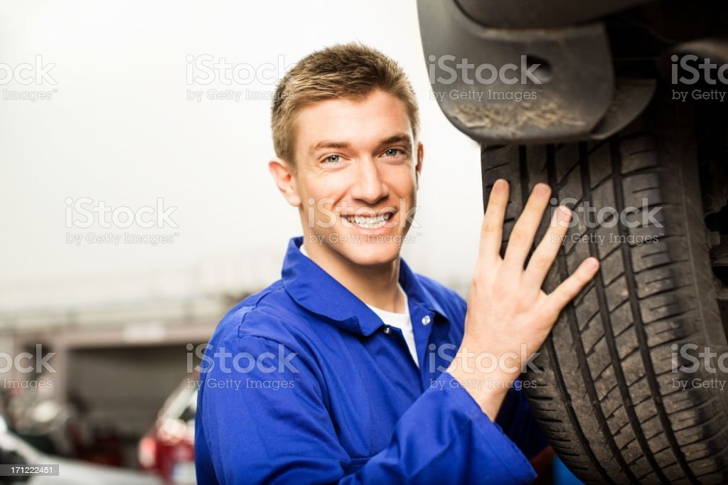 Young Mechanic Changing A Tyre stock photo