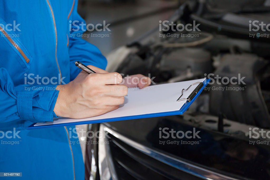 Young mechanic engineer taking a note and examining a vehicle stock photo