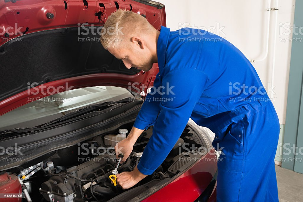 Young Mechanic Repairing Car stock photo