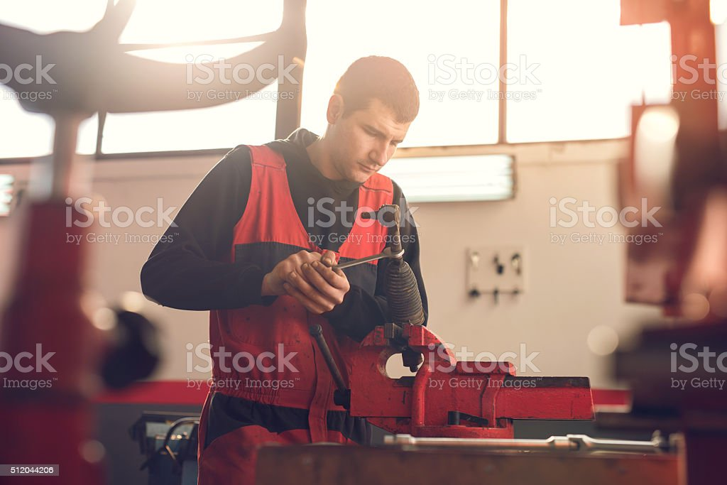 Young mechanic repairing machine part on a clamp. stock photo