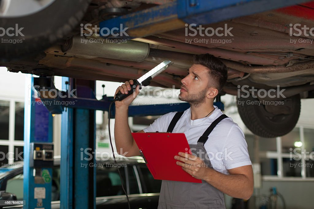 Young mechanic underneath a car inspecting the chassis stock photo