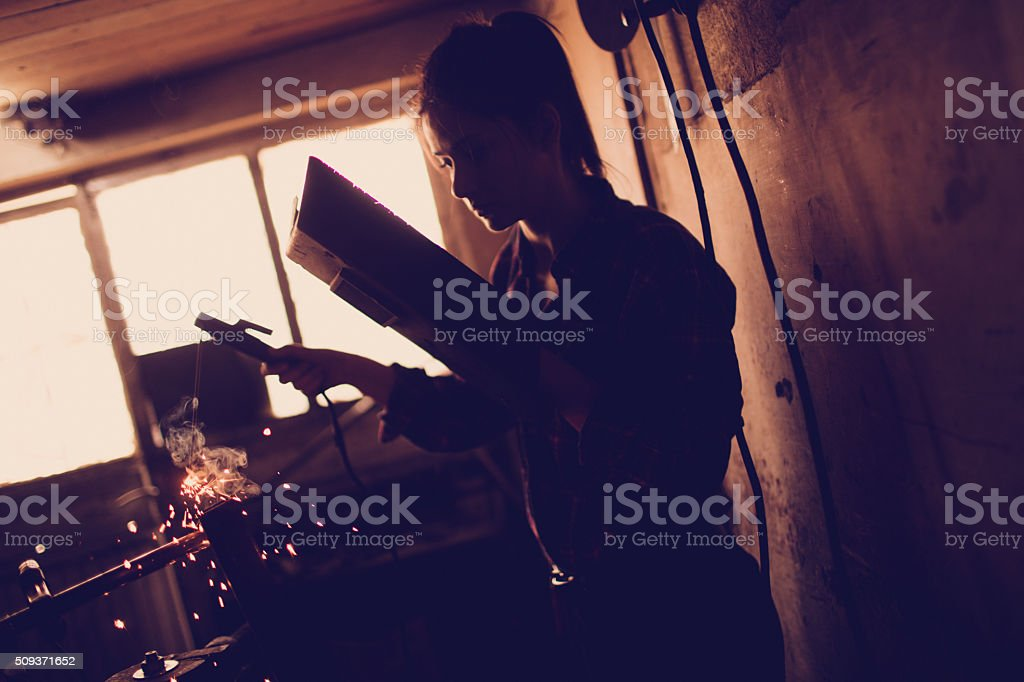 Young mechanic using a welding machine stock photo