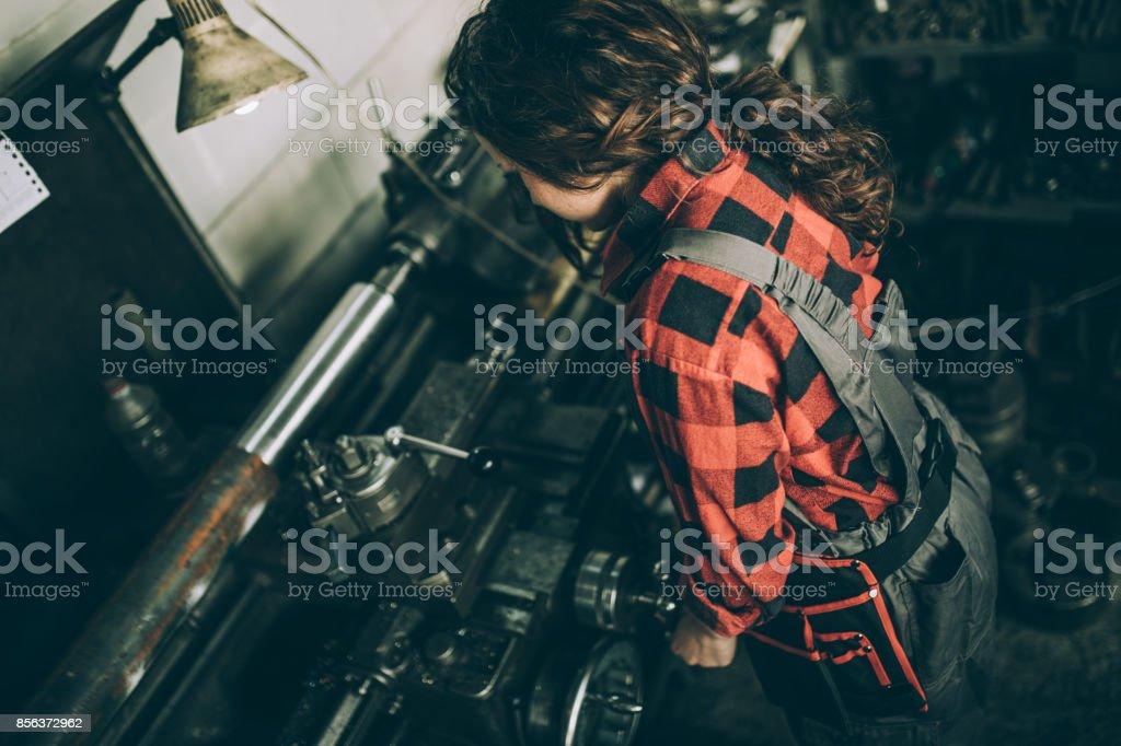 One woman, working in workshop, she has skills.