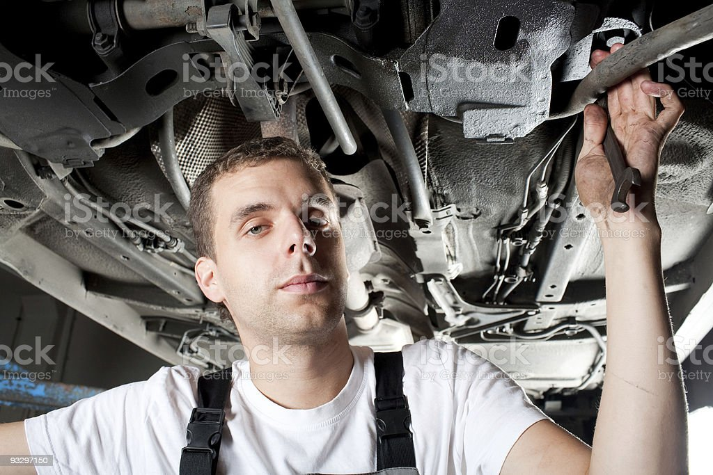 Young Mechanic working below car in uniform royalty-free stock photo