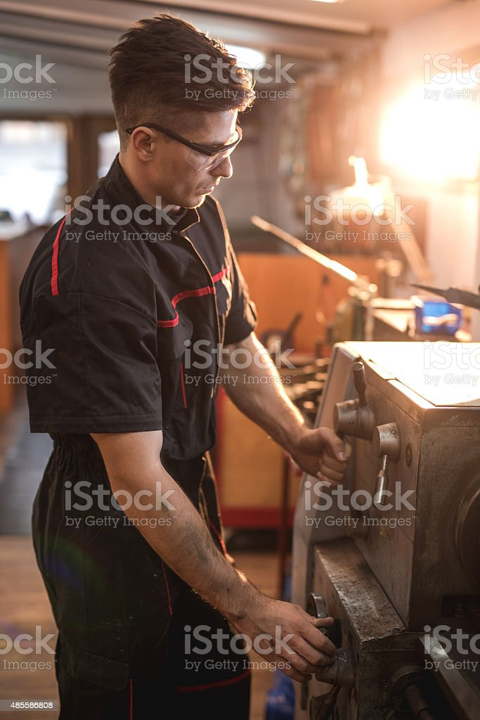 Young mechanic working on lathe machine in a workshop. stock photo