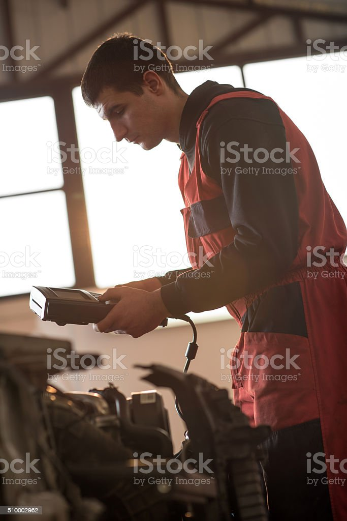 Young mechanic working with multimeter in auto repair shop. stock photo