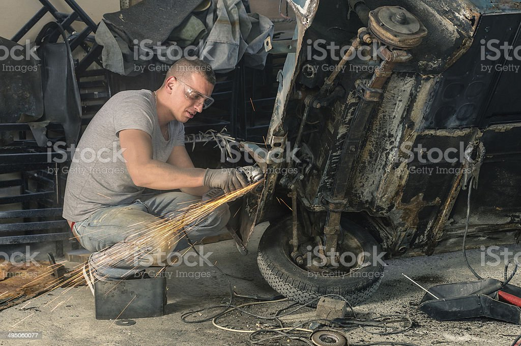 Young mechanical worker repairing an old vintage car body stock photo