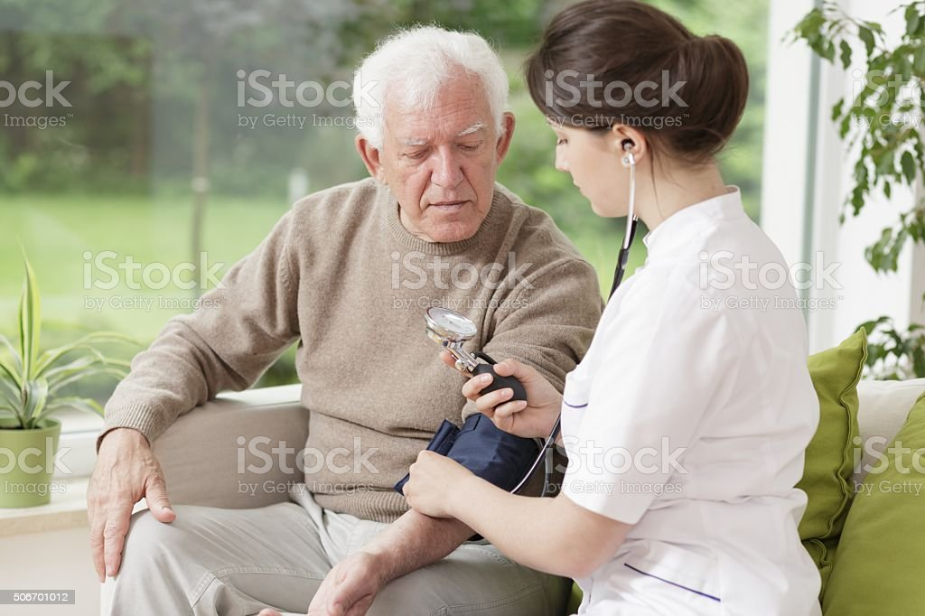 Young medic taking blood pressure stock photo