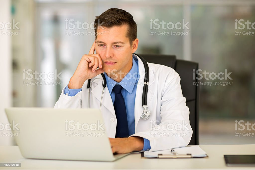 young medical doctor using laptop in office stock photo