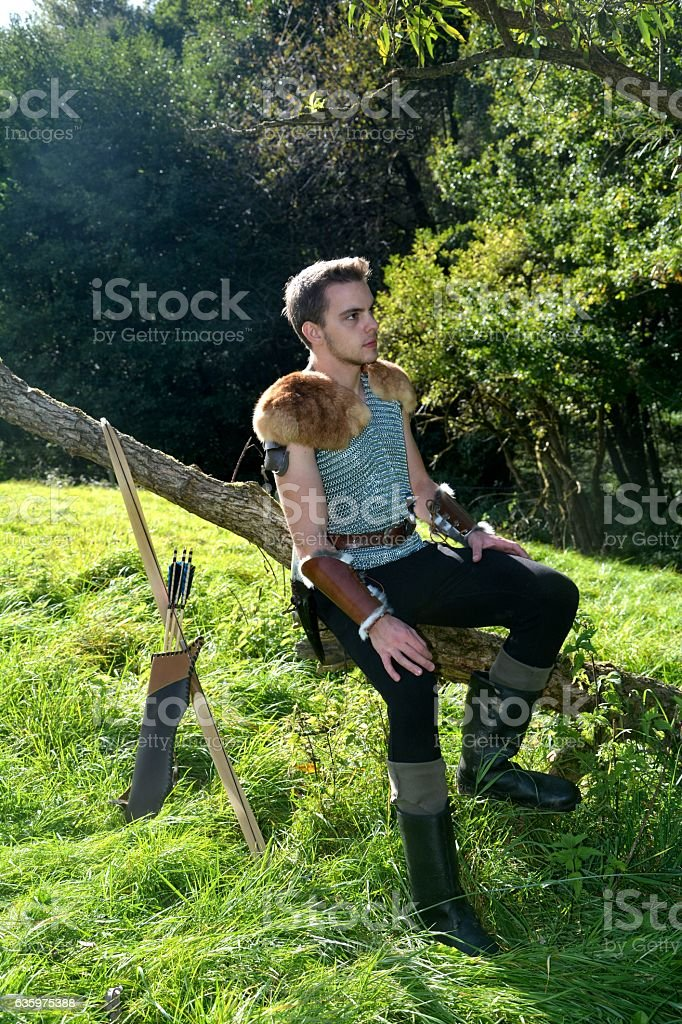Young Medieval dressed man, sits on branch and looks aside stock photo
