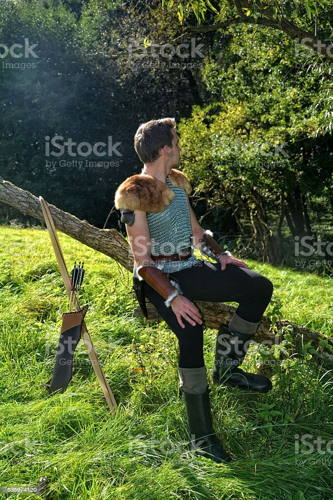 Young Medieval dressed man, sits on branch,  and looks backwards stock photo