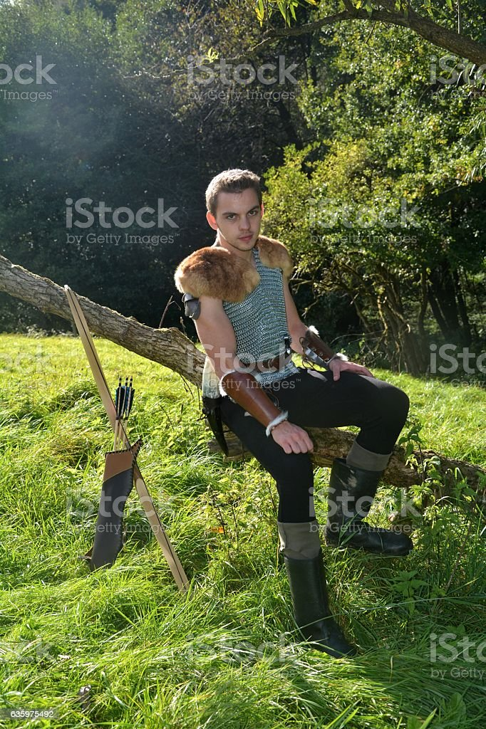 Young Medieval dressed man, sits on branch  and looks forwards stock photo