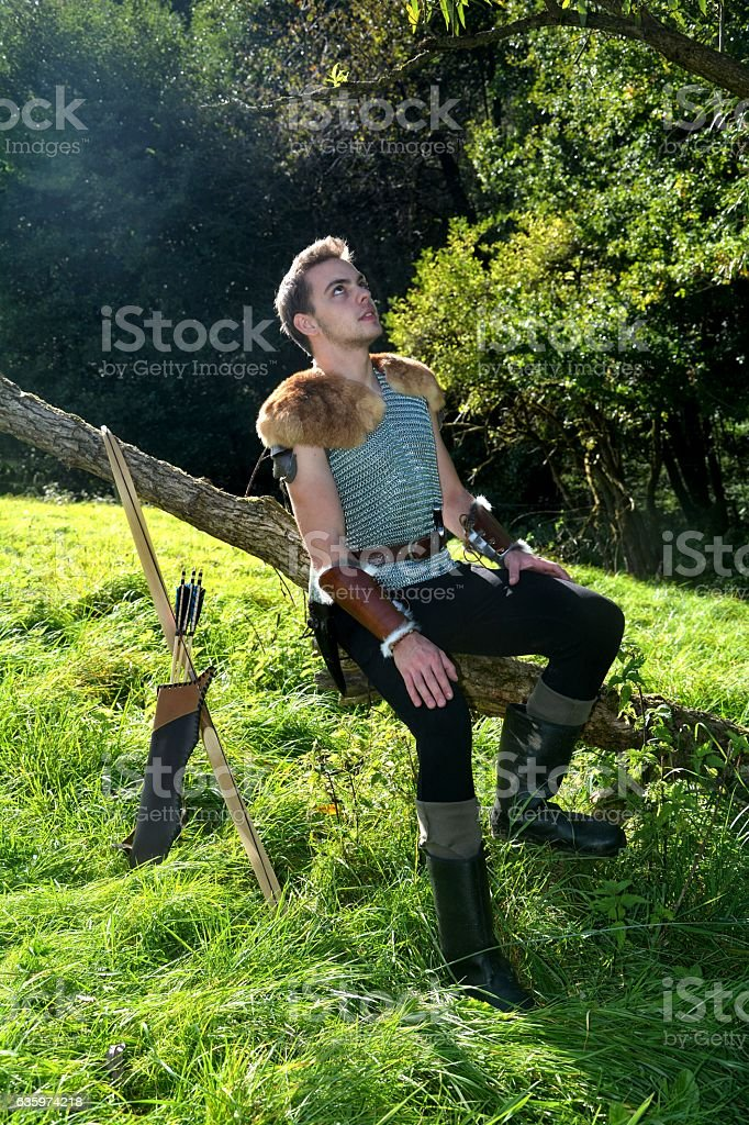 Young Medieval dressed man, sits on branch, and looks upwards stock photo
