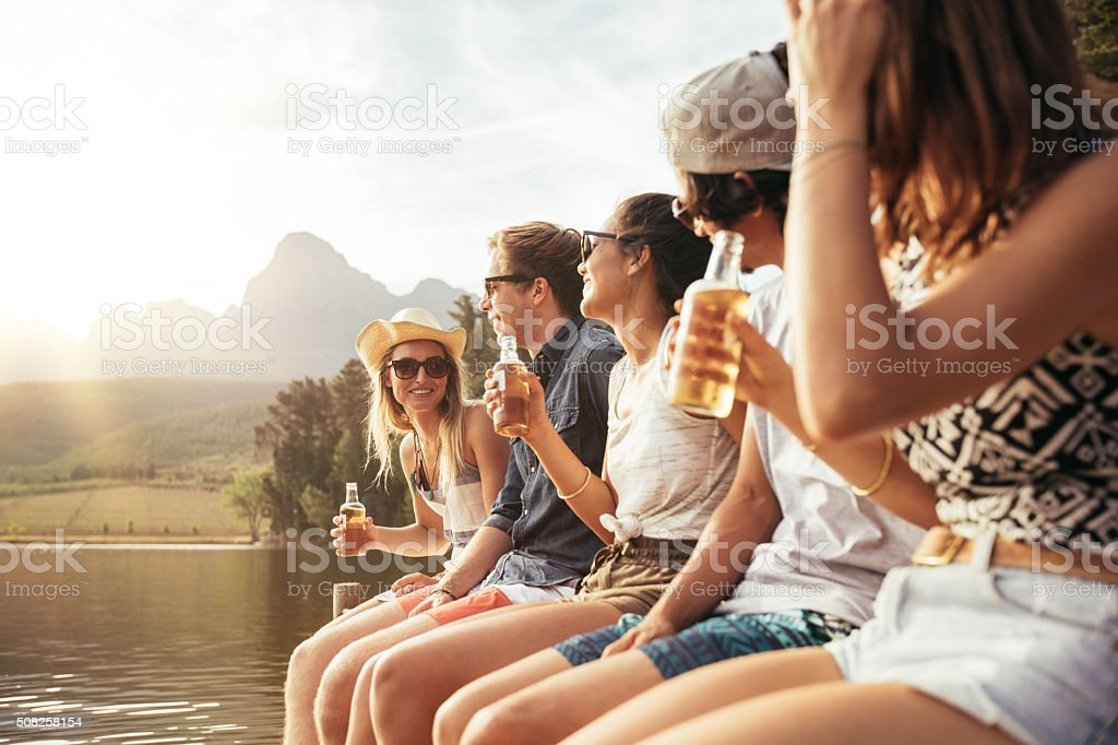 Young men and woman sitting on jetty with beers stock photo