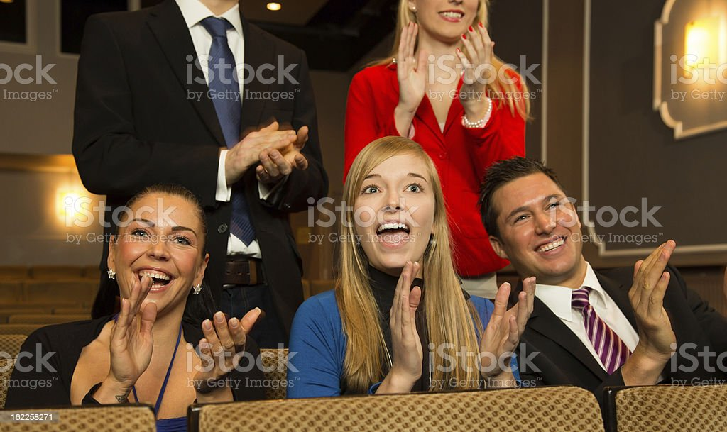 Young men and women clapping in a theater royalty-free stock photo