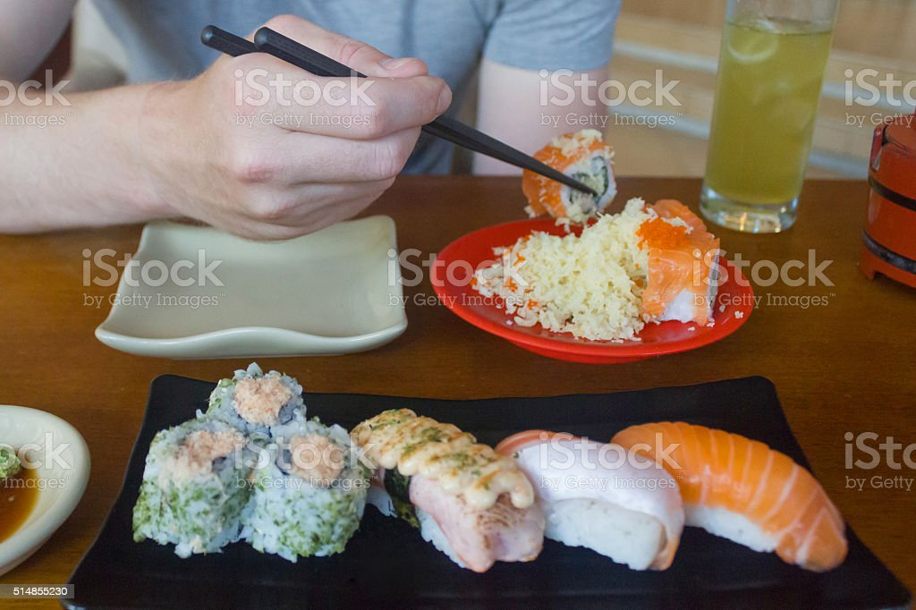Young men eating salmon sushi roll stock photo
