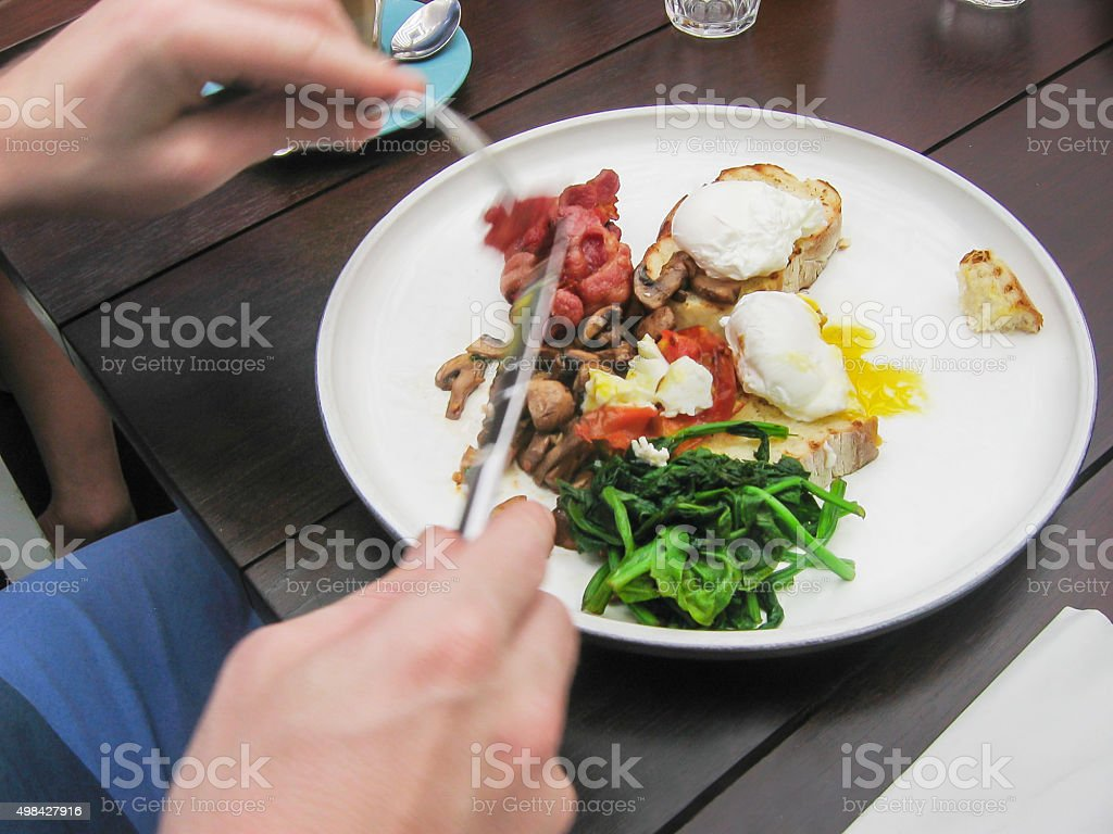 Young men eating vegetable, bacon, and poached eggs stock photo