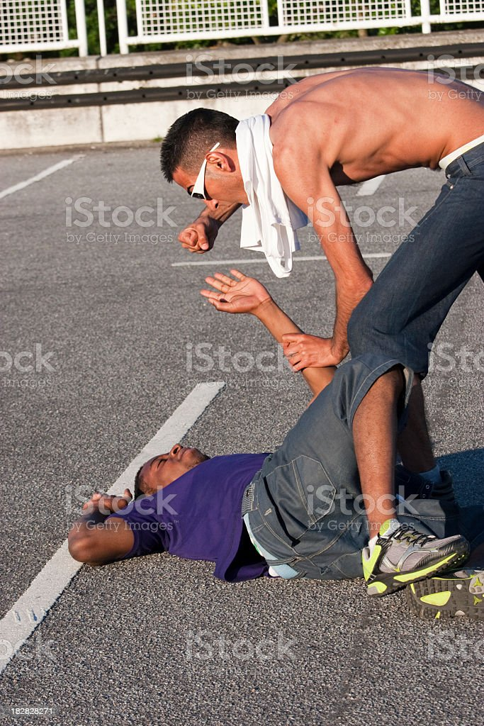Young men fighting on the ground stock photo