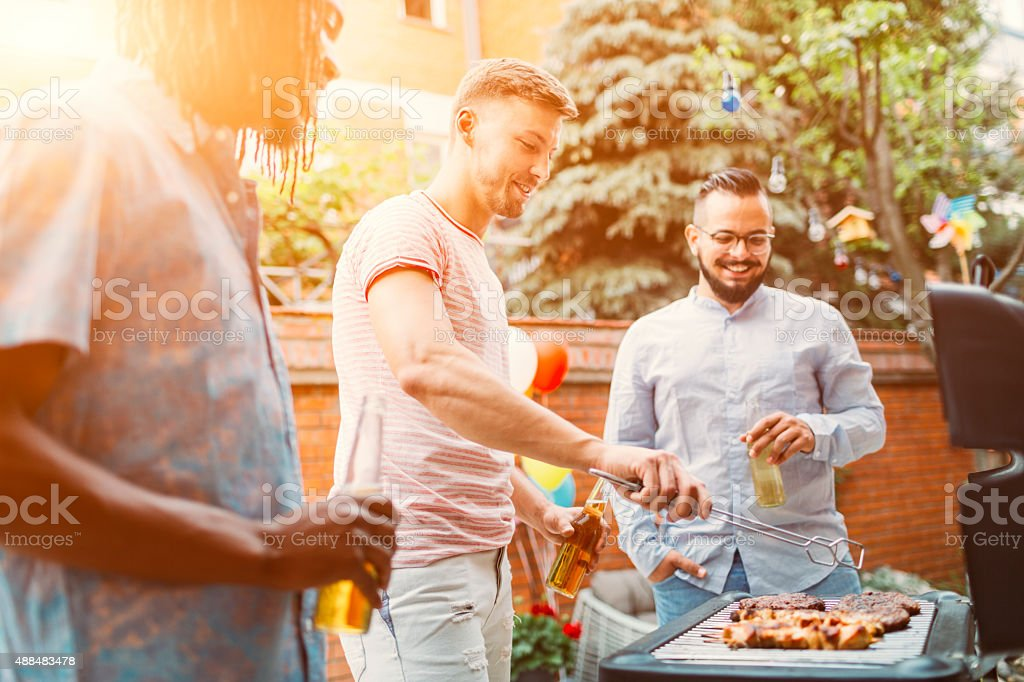 Young Men Grilling Meat At Barbecue Party. stock photo