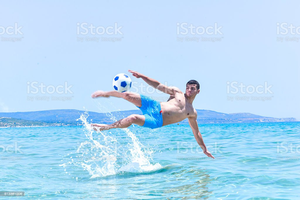Young men making an acrobatic kick ball in the sea stock photo