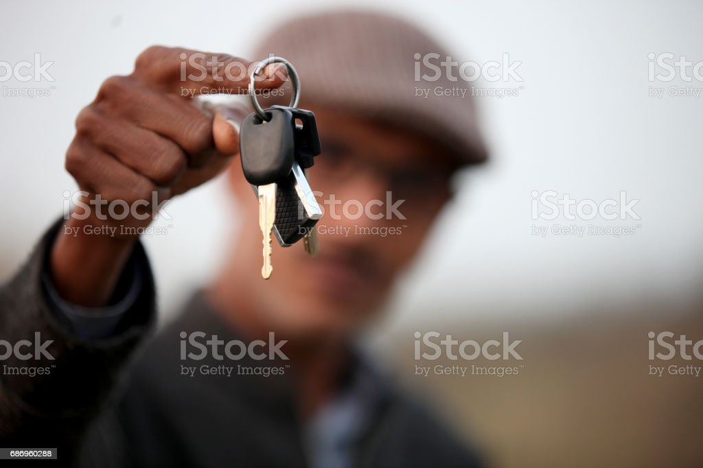 Young men offering key stock photo