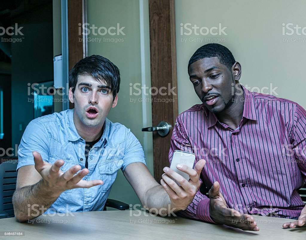 Young Men Office Workers Shocked By Text Message stock photo