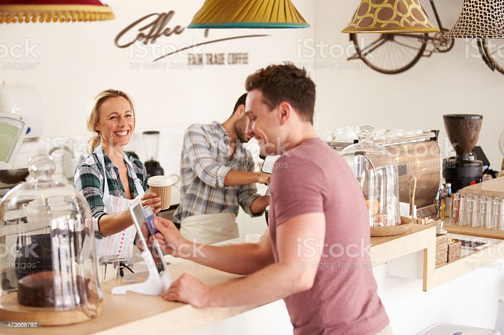 Young men paying for order in a cafe stock photo
