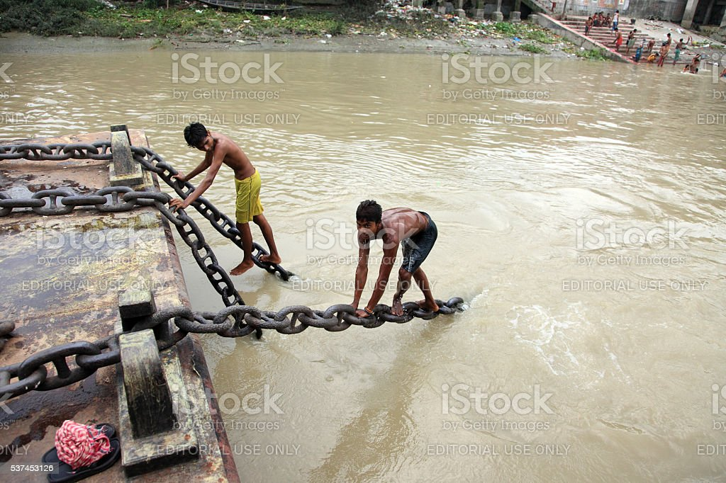 Young men performs stunt on a moving boat stock photo