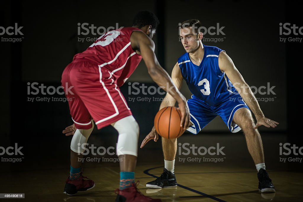 Young men playing basketball in a gymnasium stock photo