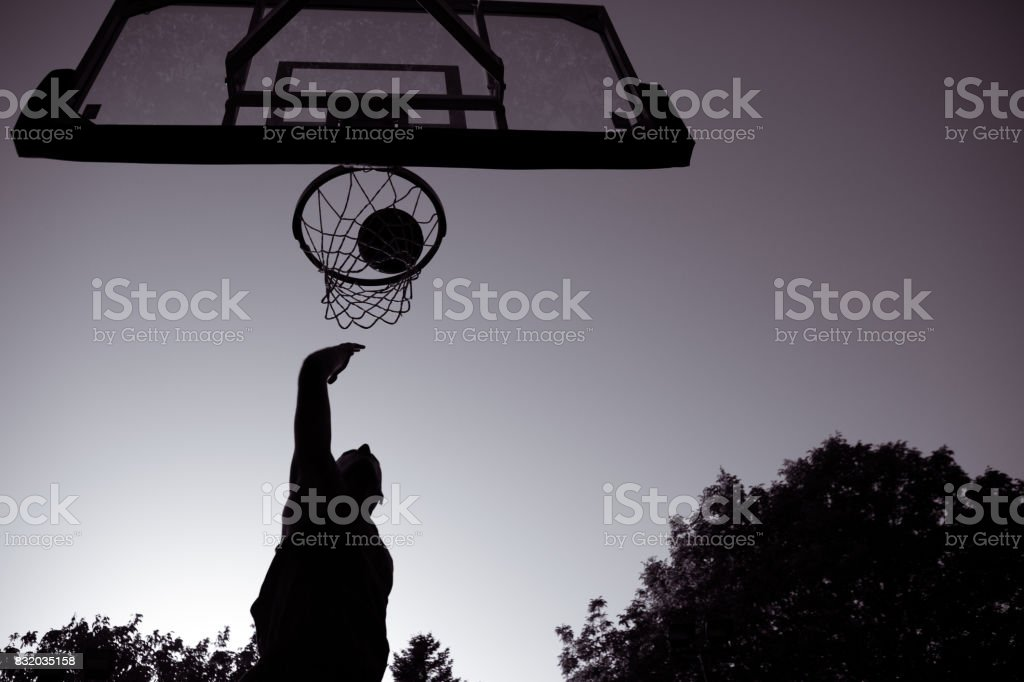 Young men playing basketball on outdoor court stock photo