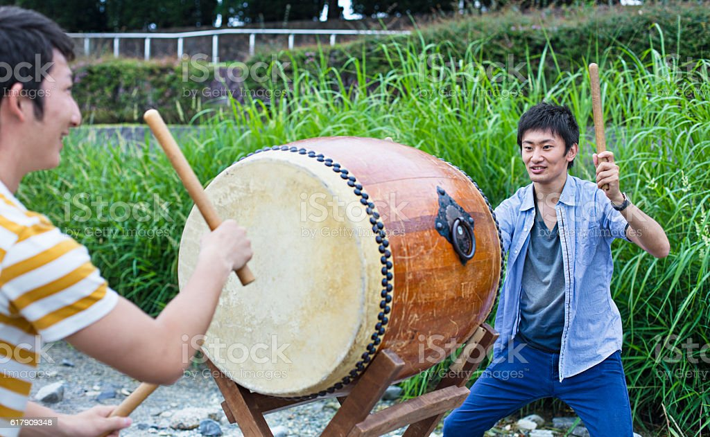Young men playing japanese taiko drum stock photo