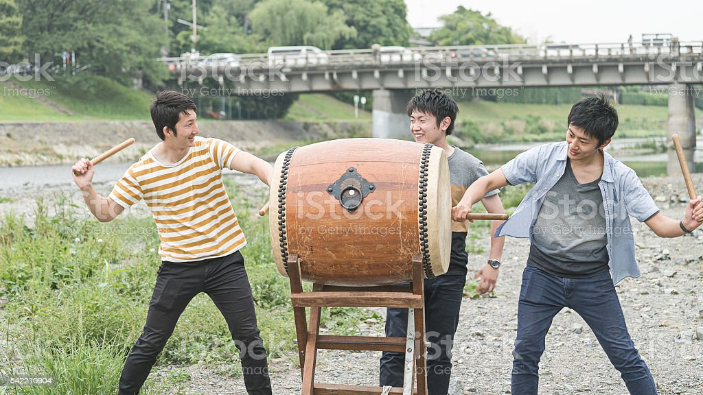 Young men playing Japnese drum in an open firld stock photo