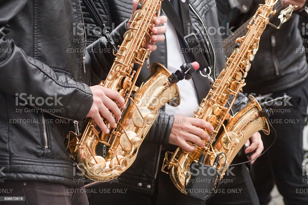 Young men playing saxophone, popular music concert, leather jackets. stock photo