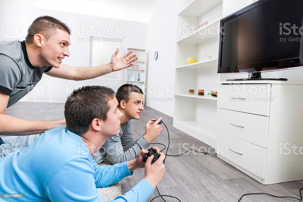 Young men playing video games. stock photo